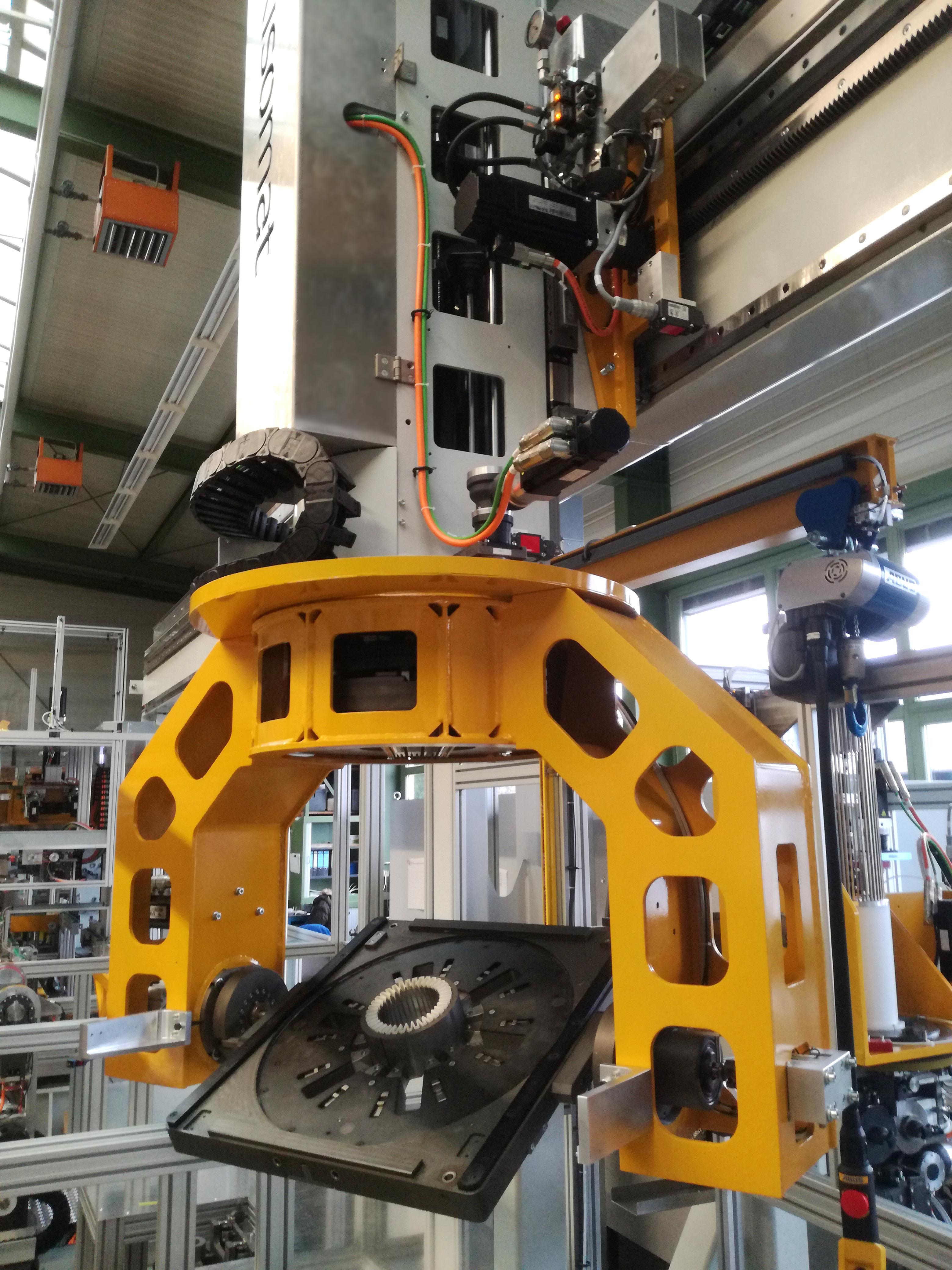 W linii produkcyjnej stojanów firmy Risomat przedmiot obrabiany i jego nośnik są transportowane pomiędzy stacjami obróbki za pomocą suwnicy bramowej.